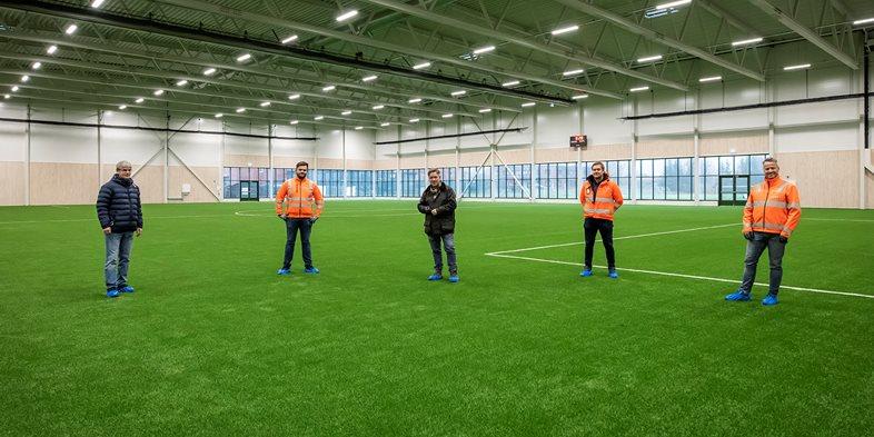 Representanter fra byggherre Drammen Eiendom KF og entreprenøren Peab inne i Åssiden fotballhall.